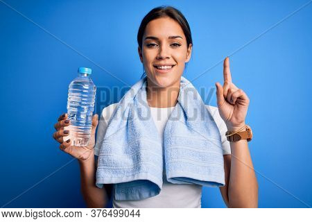 Young beautiful brunette sportswoman wearing towel drinking bottle of water to refreshment surprised with an idea or question pointing finger with happy face, number one