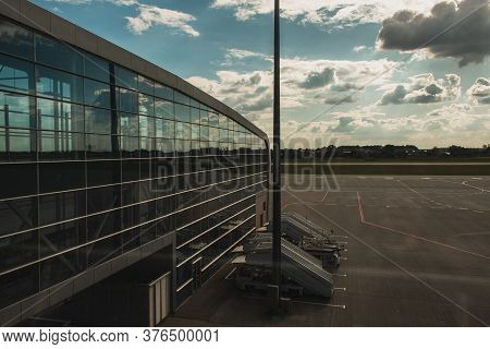Copenhagen, Denmark - April 30, 2020: Facade Of Airport With Aerodrome And Cloudy Sky At Background