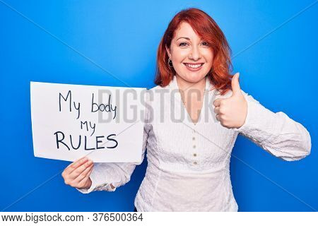 Young redhead woman asking for women rights holding paper with my body my rules message smiling happy and positive, thumb up doing excellent and approval sign