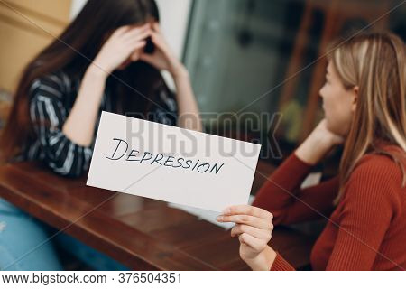 Hidden Depression Concept. Sad Woman With Psychologist Holding White Sheet Paper Labeled Word Depres