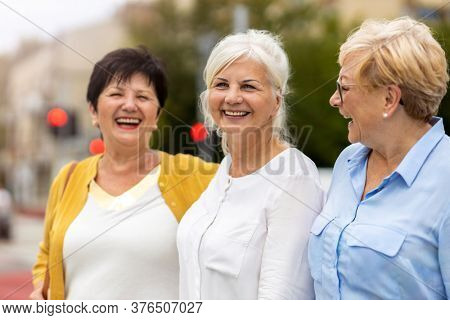 Three senior female friends having good time together