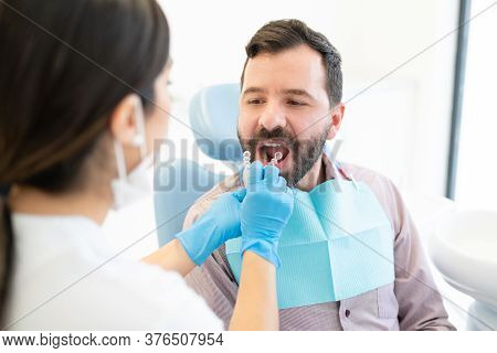 Female Orthodontist With Invisible Retainer Examining Mid Adult Man