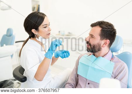 Female Doctor Examining Mid Adult Man Sitting On Chair At Dental Clinic