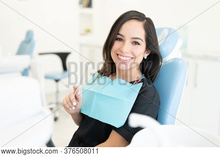 Smiling Caucasian Mid Adult Woman Holding Toothbrush In Dental Clinic