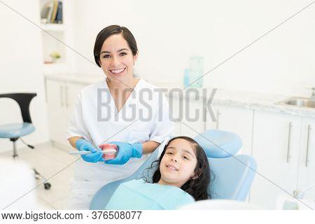 Smiling Female Dentist Holding Smile Design Model While Little Girl Lying On Chair