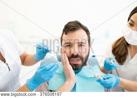 Mid Adult Hispanic Man Suffering From Toothache And Visiting A Dental Clinic