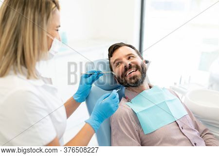 Female Doctor Checking Mid Adult Man Sitting On Chair At Dental Clinic