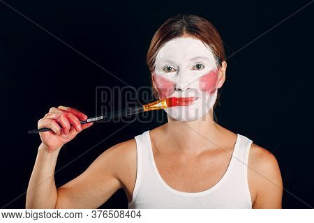 Young Woman Applying Make-up, Paints Face With Painting Brush And Makeup. How Not To Do Make Up Conc