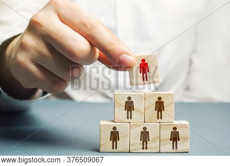 A Hand Places A Mentor Leader At The Head Of A Group Of People. Team Building, Hierarchical Power Ve