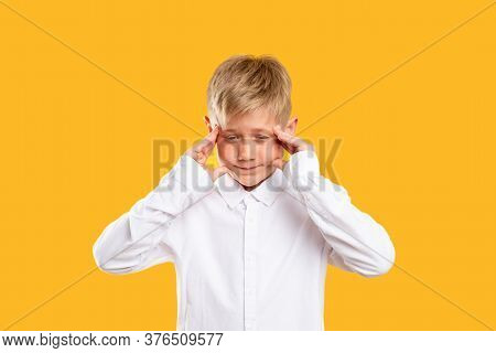 Child Anxiety. Stress Headache. Troubled Boy In White Shirt Clutching Head Isolated On Orange Backgr