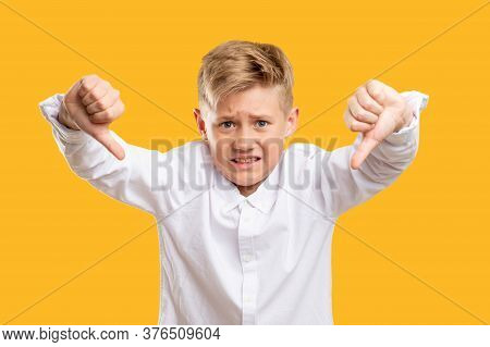 Dislike Gesture. Awful Idea. Dissatisfied Boy In White Shirt Showing Thumbs Down Isolated On Orange.