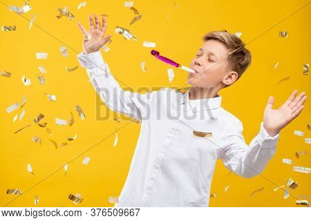 Birthday Boy Portrait. Fun Celebration. Amused Kid Blowing Party Horn In Confetti Rain Isolated On O
