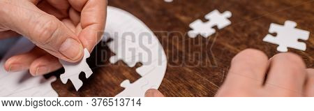 Partial View Of Diseased Senior Man Combining Jigsaw Puzzle For Dementia Therapy, Horizontal Image