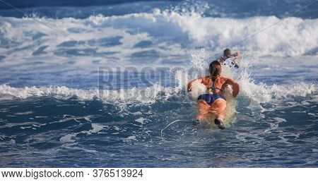Surfer Girl Waiting For A Wave. Surfer School. Beautiful Young Woman In Swimsuit Goes Into Ocean In