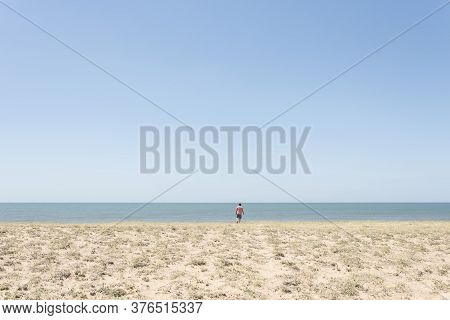 Lonely Beach On The Coast Of Uruguay, In Summer, Young Man Seen From Behind Going To The Sea