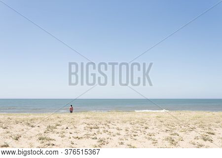 Lonely Beach On The Coast Of Uruguay, In Summer, Young Man Seen From Behind Looking At The Sea