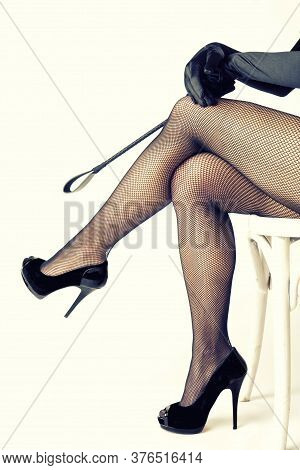 Sexy Dominatrix Woman In Fishnet Stockings Holding Riding Crop, Isolated On White Background.