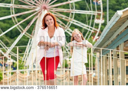Family Portrait. Mother And Daughter Have Fun Together At An Amusement Park. Ferris Wheel In The Bac