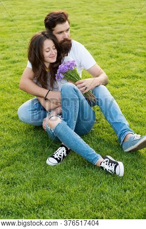 Flowers Brighten Day. Bearded Man Give Flowers To Sexy Woman. Couple In Love Relax On Green Grass. F