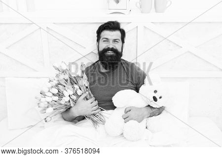 Birthday Holiday. Fresh Flowers. Bearded Hipster In Bed. Valentines Day Gift. Man Hold Bouquet Relax