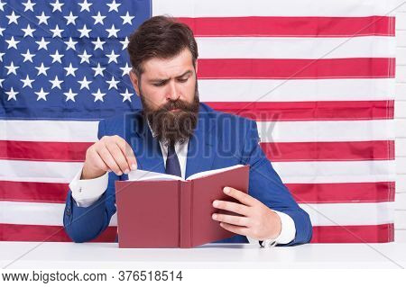 English Reading. American Bibliophile. Bearded Man Read Book On Usa Flag Background. Reading And Com