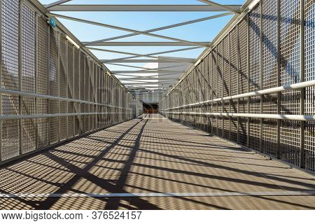 Inside Of A Modern Overhead Pedestrian Bridge Over An Expressway On A Sunny Day. Diminishing Perspec
