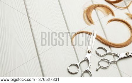 Cut Hair Curls And Thinning Scissors On A White Wooden Background. Copy Space For Text.