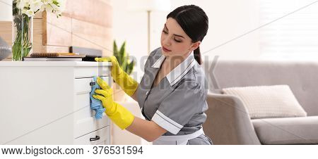 Young Chambermaid Wiping Dust From Furniture In Hotel Room. Banner Design
