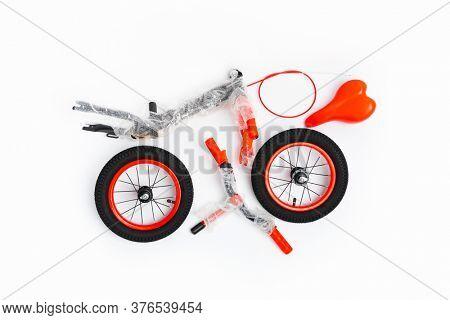 disassembled balance bike on white background