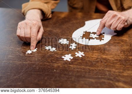 Partial View Of Senior Man Playing Jigsaw Puzzle As Dementia Therapy
