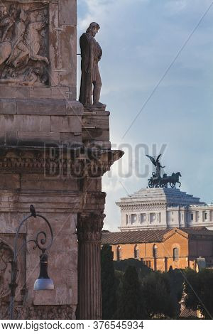 A View Of The Statue Over The Arch Of Constatine In Front Of The Equestrian Statue Of Vittorio Emanu
