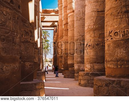 Luxor, Egypt - February 2020: Row Of Columns In Karnak Temple, Medium View. Ancient Legends On Yello