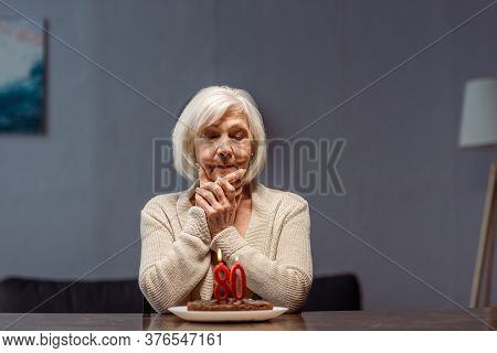 Senior, Lonely Woman Touching Face While Looking At Birthday Cake With Number Eighty And Burning Can