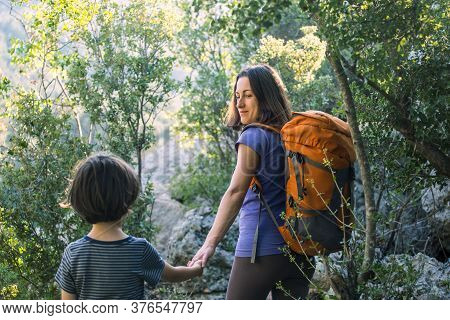 A Woman Walks With Her Son Through The Forest, The Boy With His Mother Go Hiking, A Child With A Bac
