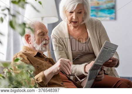 Selective Focus Of Attentive Senior Couple Reading Newspaper Together