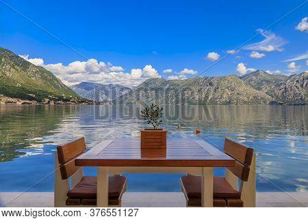 Waterfront Table At A Restaurant With A View Of Kotor Bay Of Kotor Bay Or Boka Kotorska In The Backg