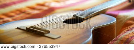 Traditional Acoustic Wooden Guitar Body With Strings And Neck Put On Striped Blanket On Bed At Sunli