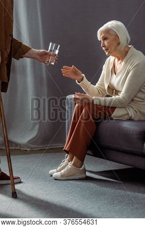 Partial View Of Senior Man Giving Glass Of Water To Wife Feeling Bad And Sitting On Sofa