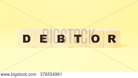 Word Debtor Made With Black Letters On Small Wooden Cubes On Yellow Background At Bright Light Close