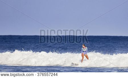 Beautiful Young Woman Learns To Stand On A Surfboard. Surfer School. Woman In Swimsuit In Hot Summer