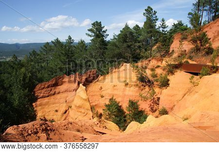 View Of Colorful Orange Ochre Cliffs With Pine Trees And Blue Sky At The Natural Regional Park In Ro