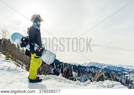 Snowboarder Freerider In The Mountains Is Preparing To Descend On The Background Of Snow-capped Moun