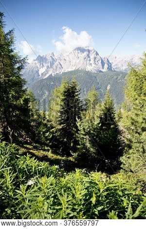 View Of The Mountain Range Of The Italian Dolomites, Green Trees Blue Sky With Clouds