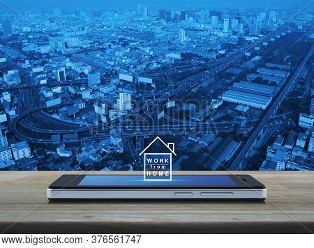 Work From Home Flat Icon On Modern Smart Mobile Phone Screen On Wooden Table Over City Tower, Street