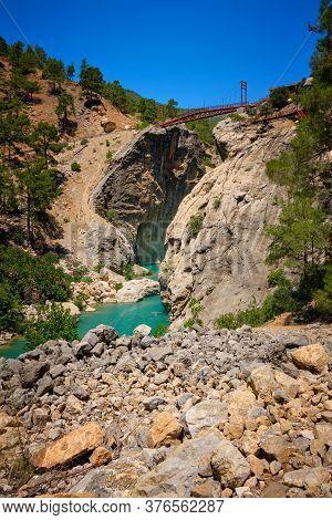 Metal Pedestrian Bridge Over The Gorge And Mountain River. Yerkopru Waterfall, Ermenek River, Mersin
