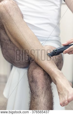 The Man Is Holding A Clipper In His Hand And Is Cutting His Calf Hair.