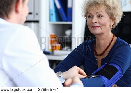 Portrait Of Male Doctor Measuring Blood Pressure Of Beautiful Senior Woman. Blonde Female Sitting On