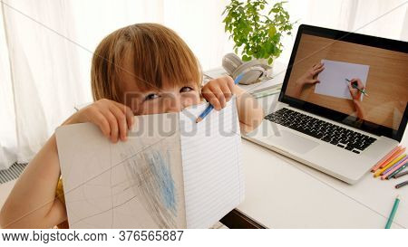 High Angle Of Cute Child Showing Notebook With Doodles And Looking At Camera While Watching Drawing