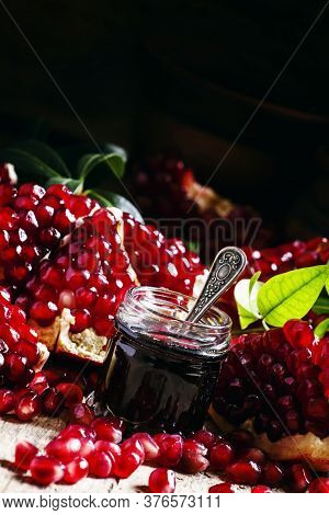 Homemade Pomegranate Jam In A Glass Jar With A Spoon, Fresh Open Pomegranate On A Dark Background, S