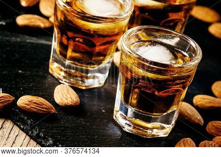 Brandy And Almonds, Small Glasses On A Dark Background, Selective Focus